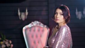 Retrato de la mujer atractiva de la moda que presenta en la igualación del vestido brillante con vista lateral de las chispas almacen de metraje de vídeo