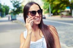 Retrato de la mujer atractiva que habla en el teléfono en la ciudad Imágenes de archivo libres de regalías