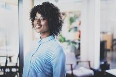 Retrato de la mujer bastante africana de los jóvenes con el afro que mira y que sonríe la cámara Interior en fondo en moderno Imágenes de archivo libres de regalías