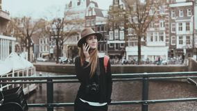Retrato de la mujer bastante caucásica que hace una llamada El fotógrafo joven hermoso habla en el teléfono que sonríe alegre 4K almacen de video