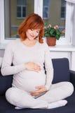 Retrato de la mujer bastante embarazada que se sienta en casa Imagen de archivo