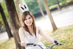 Retrato de la mujer bastante joven con la bicicleta en una sonrisa del parque Fotografía de archivo libre de regalías