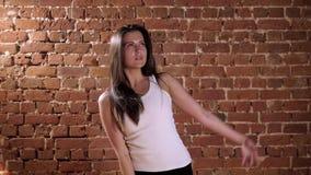 Retrato de la mujer bastante joven que hace yoga en estudio del desván en fondo del ladrillo metrajes