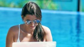 Retrato de la mujer bonita del freelancer en las gafas de sol que trabajan en la piscina usando el ordenador portátil metrajes
