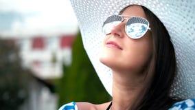 Retrato de la mujer bonita elegante en sombrero y gafas de sol que sonríe y que liga el hombro desnudo conmovedor almacen de metraje de vídeo
