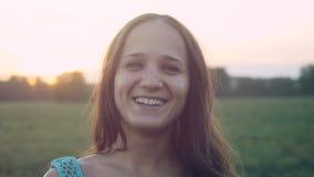 Retrato de la mujer bonita en la puesta del sol en el campo Foto de archivo libre de regalías