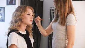 Retrato de la mujer bonita, joven con el artista de maquillaje en el trabajo almacen de metraje de vídeo