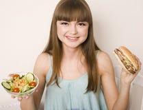 Retrato de la mujer bonita joven con la hamburguesa y la ensalada, tomando la decisión Fotografía de archivo libre de regalías