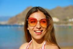 Retrato de la mujer bonita joven con las gafas de sol en la playa foto de archivo libre de regalías