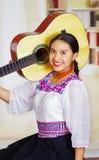 Retrato de la mujer bonita joven que lleva la ropa andina tradicional hermosa, sentándose abajo deteniendo la guitarra acústica Imágenes de archivo libres de regalías