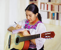 Retrato de la mujer bonita joven que lleva la ropa andina tradicional hermosa, sentándose con jugar de la guitarra acústica Imágenes de archivo libres de regalías