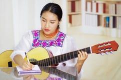 Retrato de la mujer bonita joven que lleva la ropa andina tradicional hermosa, sentándose con jugar de la guitarra acústica Imagen de archivo libre de regalías