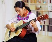 Retrato de la mujer bonita joven que lleva la ropa andina tradicional hermosa, sentándose con jugar de la guitarra acústica Fotografía de archivo