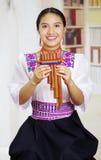 Retrato de la mujer bonita joven que lleva la ropa andina tradicional hermosa, sentándose con mientras que juega Fotos de archivo libres de regalías