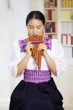 Retrato de la mujer bonita joven que lleva la ropa andina tradicional hermosa, sentándose con mientras que juega Foto de archivo