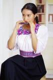 Retrato de la mujer bonita joven que lleva la ropa andina tradicional hermosa, sentándose con mientras que juega Foto de archivo libre de regalías