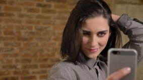 Retrato de la mujer bonita joven que toma el selfie y que toca su pelo, sonrisa, feliz, fondo del edificio de ladrillo metrajes