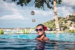 Retrato de la mujer bronceada hermosa en el traje de baño negro que se relaja en balneario de la piscina Día de verano caliente y Imagenes de archivo