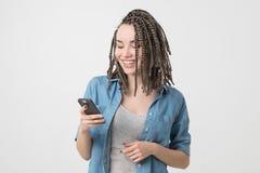 Retrato de la mujer caucásica con panes que lee SMS en el teléfono Imagen de archivo libre de regalías