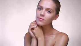 Retrato de la mujer caucásica desnuda que está pareciendo fresca y está cuidando sobre su piel dentro del estudio blanco almacen de metraje de vídeo