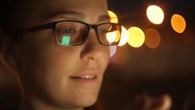 Retrato de la mujer caucásica hermosa joven que usa el control elegante de la mano del teléfono al aire libre en la noche de la c almacen de video