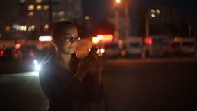 Retrato de la mujer caucásica hermosa joven que usa el control elegante de la mano del teléfono al aire libre en la noche de la c almacen de metraje de vídeo