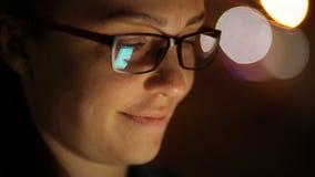 Retrato de la mujer caucásica hermosa joven que usa el control elegante de la mano del teléfono al aire libre en la noche de la c metrajes