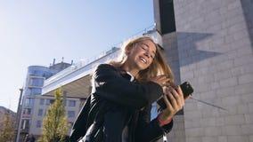 Retrato de la mujer caucásica joven atractiva que usa el app en mandar un SMS del smartphone y de la ojeada mientras que camina e almacen de video