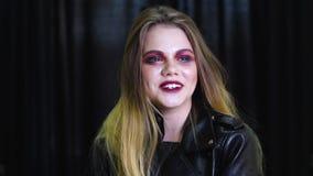 Retrato de la mujer caucásica joven con el pelo rubio que presenta y que ríe en fondo negro metrajes