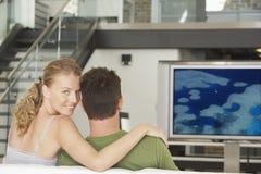 Retrato de la mujer caucásica joven con película de observación del hombre en la televisión en sala de estar Foto de archivo
