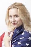 Retrato de la mujer caucásica joven hermosa envuelta en bandera americana contra el fondo blanco Foto de archivo