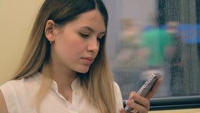 Retrato de la mujer caucásica joven que monta en un coche de subterráneo y que usa Smartphone metrajes