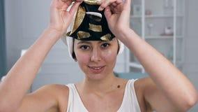 Retrato de la mujer caucásica joven que quita rejuveneciendo la máscara de oro cosmética del tejido en cara almacen de video