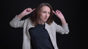 Retrato de la mujer caucásica morena de mediana edad que baila modesto en fondo negro metrajes