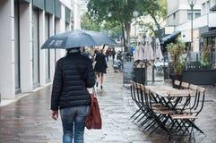 Retrato de la mujer con el paraguas en la calle de los adoquines con la terraza vacía del restaurante Fotografía de archivo libre de regalías