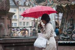 Retrato de la mujer con el paraguas rojo en lugar principal de los adoquines en la ciudad Foto de archivo libre de regalías
