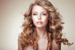 Retrato de la mujer con el pelo muy rizado bronceado que fluye hermoso Imagenes de archivo