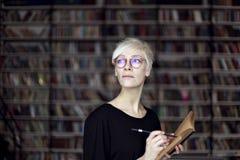 Retrato de la mujer con el pelo rubio y las lentes en una biblioteca, libro abierto Estudiante del inconformista Concepto de la e Foto de archivo