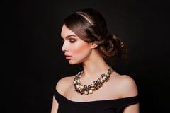 Retrato de la mujer con joyería que lleva perfecta del maquillaje y del peinado Foto de archivo