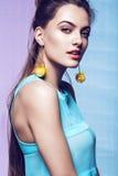 Retrato de la mujer con los pendientes amarillos en vestido azul Imagenes de archivo
