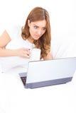 Retrato de la mujer confusa y sorprendida que usa el ordenador portátil que bebe c Fotografía de archivo