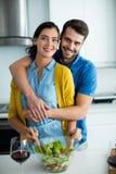 Retrato de la mujer de abarcamiento del hombre en la cocina Imagen de archivo libre de regalías