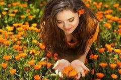 Retrato de la mujer de la belleza con las flores. Goce moreno feliz libre Foto de archivo libre de regalías