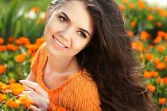 Retrato de la mujer de la belleza con las flores. Goce moreno feliz libre Foto de archivo