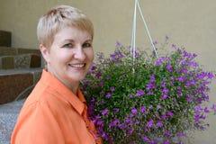 Retrato de la mujer de los años medios con las flores decorativas Imagen de archivo libre de regalías