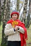 Retrato de la mujer de los años medios con las hojas de arce amarillas en manos Foto de archivo libre de regalías