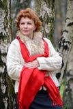 Retrato de la mujer de los años medios contra la perspectiva de abedules en la madera Imagen de archivo libre de regalías