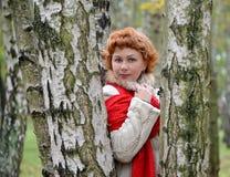 Retrato de la mujer de los años medios entre abedules en la madera Imagen de archivo