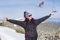 Retrato de la mujer de los turistas con los brazos abiertos que goza del sol del invierno Foto de archivo