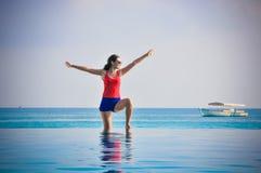 Retrato de la mujer de mirada asiática joven que coloca la piscina cercana y la playa tropical de levantamiento de las manos en M Imagenes de archivo